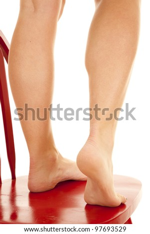 The back of a woman's legs standing on a red chair. - stock photo