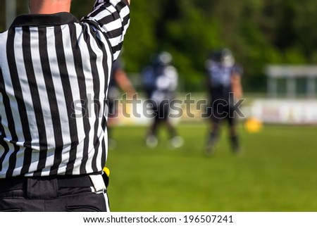 the back of an American football referee with blurred players and  field in the background - stock photo