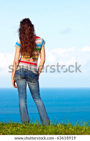 The back of an attractive young woman relaxing and looking at the ocean view - stock photo
