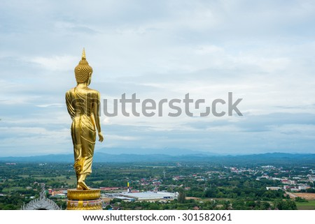 The back of the standing Buddha statue on a mountain Wat Phra That Khao Noi, Nan Province, Thailand.
