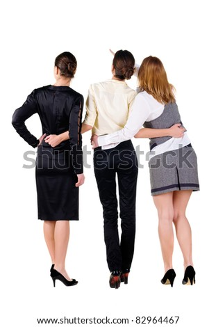 The back of three beautiful young business woman looking at wall. Rear view. Isolated over white. - stock photo