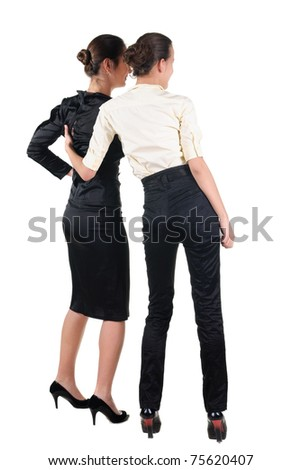 The back of two beautiful young business woman looking at wall. Rear view. Isolated over white. - stock photo