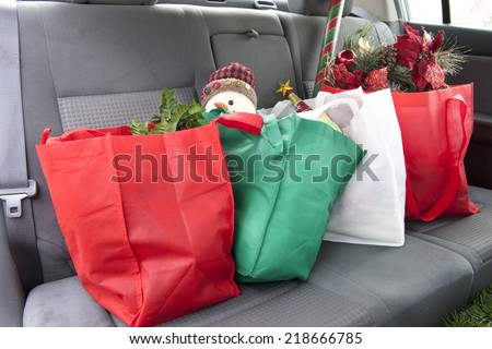 The back seat of a car with four bags of Christmas gifts and decor. - stock photo