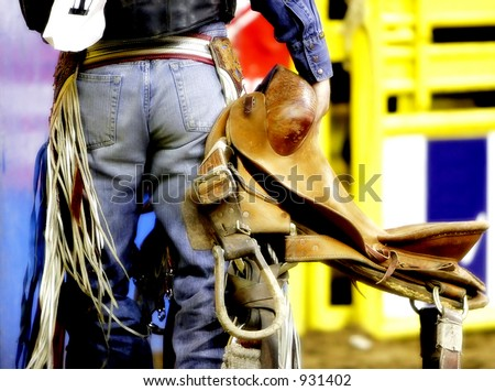 The back side of a rodeo cowboy carrying his saddle before he competes (bold colors).