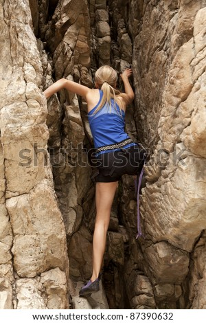 The back view of a woman rock climbing up a mountain, with ropes. - stock photo