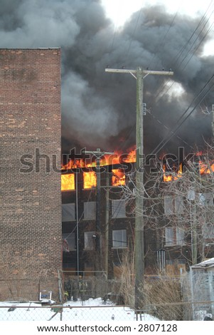 The back view of an apartment house in blazes - stock photo