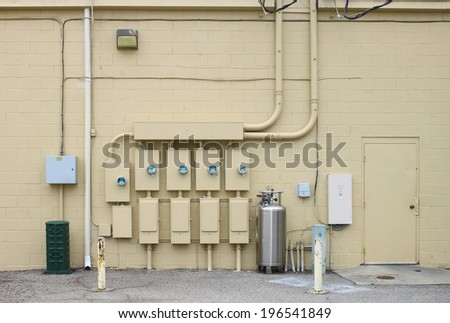 The back wall of a large coalition of businesses and the electric power,telephone,cab le and gas distribution systems that they operate off of. - stock photo