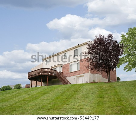 The back yard of a suburban neighborhood brick home, featuring a sloped yard and a large redwood deck. - stock photo