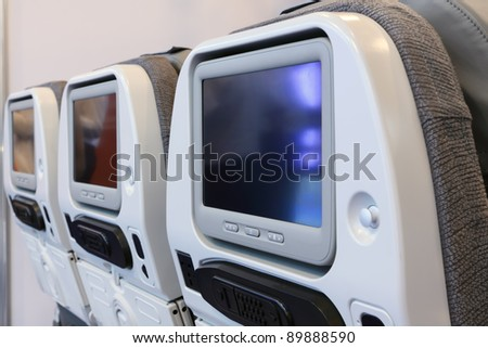 The backs of the seats in the cabin of the plane of business class with embedded in them tvs - stock photo