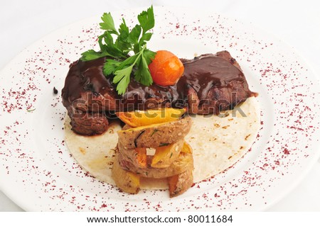 The baked meat in sauce about a potato of Idaho on a white plate - stock photo