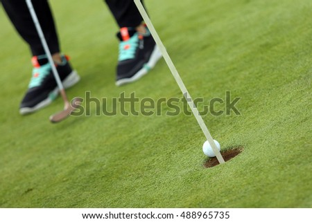 The ball falling in golf hole with black sneakers on the background