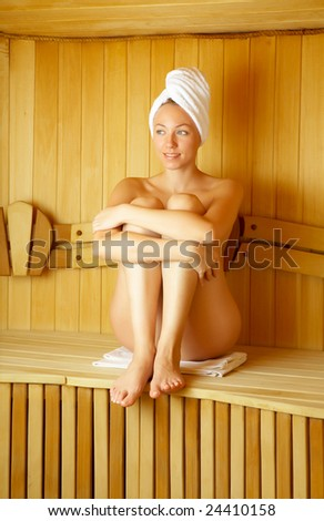 The bared girl sits in a sauna in a towel - stock photo