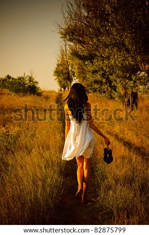 The barefoot girl in white dress with shoes in hand is on the field. Rear view - stock photo