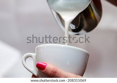 The bartender at the workplace. Female bartender makes cappuccino. The girl pouring milk in coffee. Cappuccino, bartender. - The concept of technology of making coffee. USES in articles about coffee. - stock photo