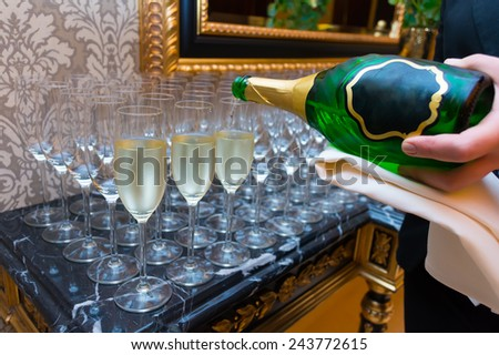 The bartender pours champagne into the empty glasses from the bottle - stock photo