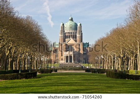 The Basilica of the Sacred Heart in Brussels ranks fifth among the largest churches in the world. The large Art Deco building lies at the end of a park way and is surrounded by trees. - stock photo