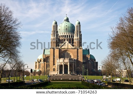 The Basilica of the Sacred Heart in Brussels ranks fifth among the largest churches in the world. The large Art Deco building is catched in the sunlight against a light-blue sky with some clouds. - stock photo