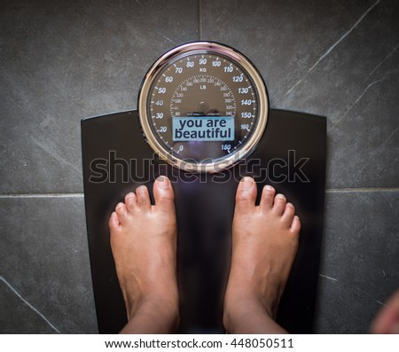 the bathroom scale that talks to you and tells the truth on the screen: you're beautiful! - stock photo