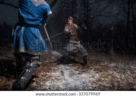 The battle between medieval knights in the style of Game of Thrones in winter forest landscapes. Spear against sword - stock photo