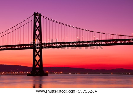 The Bay Bridge in San Francisco silhouetted against a clear sky just before sunrise. - stock photo