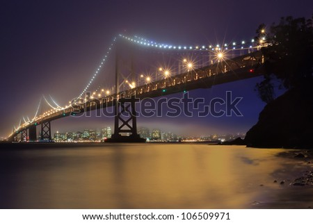 The Bay Bridge of San Francisco, California is shrouded in fog as the lights of the city and the bridge collect in the water below. - stock photo