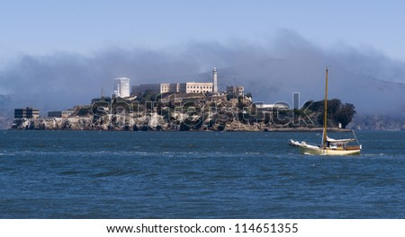 The bay in San Francisco with Alcatraz island and a sailboat passing - stock photo