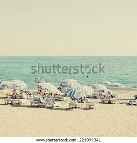 The beach and the beach umbrellas of midsummer in retro style - stock photo