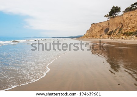 The beach at Loon Point in the seaside village of Summerland, California.  Leadbetter Point in Santa Barbara is visible on the horizon. - stock photo
