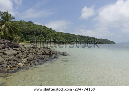 The beach beside island and blue sky with mountains in the background - stock photo