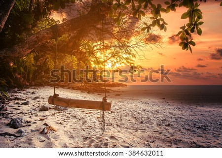 The beach in sunset with hanging wooden swing, dark environment in evening  - stock photo