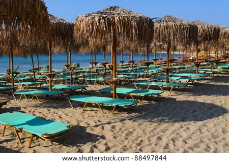 The beach near the blue sea with sun beds and umbrellas - stock photo