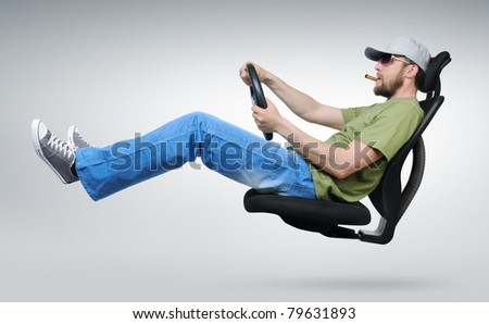 The bearded driver with a cigar while driving on an office chair - stock photo