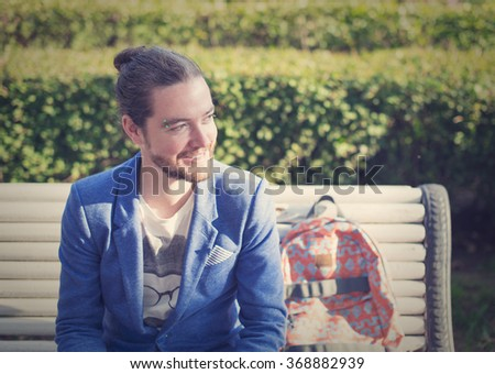 The bearded hipster photographer in blue jacket angrily smiling and looking away in a park in St. Petersburg. - stock photo