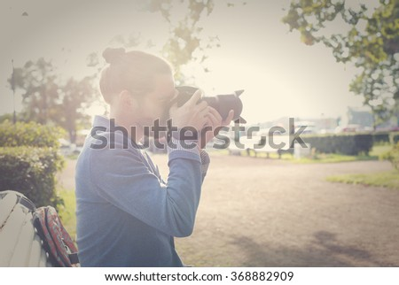 The bearded hipster photographer in blue jacket photographs in the park in the summer. - stock photo