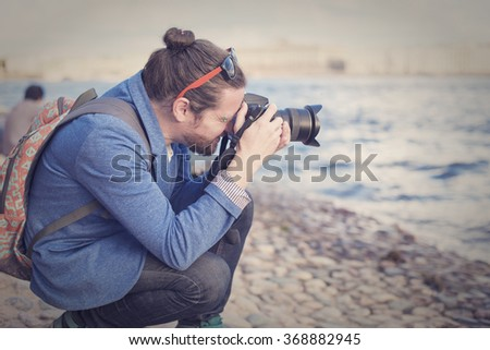 The bearded hipster photographer in blue jacket photographs on the banks of the Neva River in St. Petersburg. - stock photo