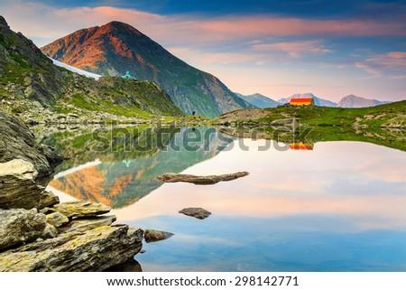 The beautiful alpine Caltun lake and colorful mountain shelter with stunning sunset,Fagaras mountains,Carpathians,Transylvania,Romania,Europe - stock photo