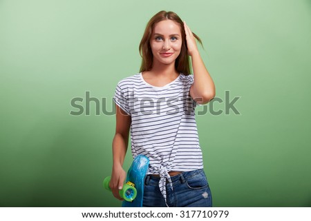 the beautiful amusing girl holds a skateboard