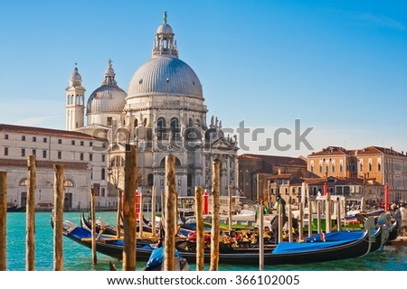 The beautiful and famous tourist destination the Basilica Santa Maria della Salute church with venetian gondolas in sunny weather on the Grand Canal, Venice, Italy - stock photo