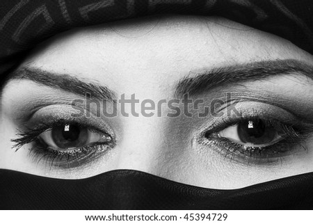 The beautiful and thoughtful eyes of an arabic woman with headscarf. Monochrome photo - stock photo