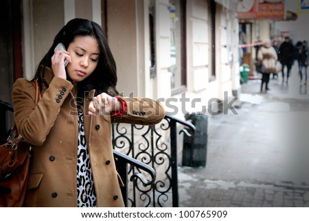 The beautiful Asian girl speaks by phone and looks at the watch