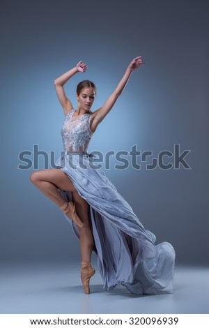 The beautiful ballerina dancing in long blue dress on blue background - stock photo