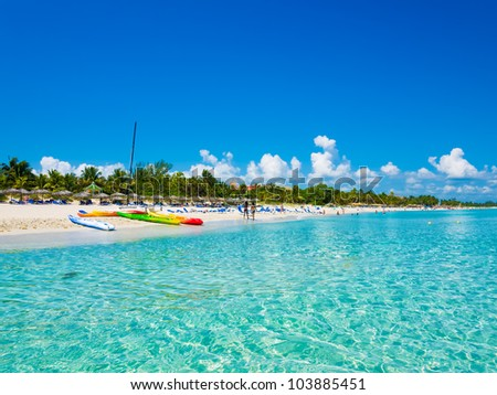 The beautiful beach of Varadero in Cuba with colorful boats and thatched umbrellas (image taken from the sea) - stock photo