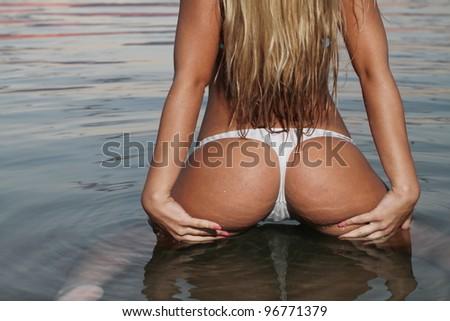 The beautiful bikini model posing against a setting sun on a body of water - stock photo