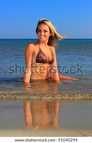 The beautiful bikini model posing on the beach - stock photo