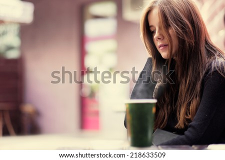 The beautiful blonde in a street cafe - stock photo