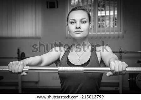 The beautiful blonde in the gym. The girl is engaged in strength training. Holding hand on barbell. Exercise, fitness, sports, health. Healthy lifestyle concept. Article about the sport
