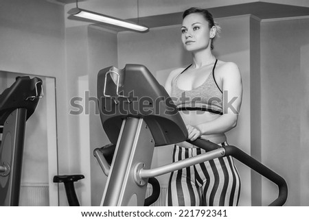The beautiful blonde on a treadmill. Black and white photography.Cute young woman exercising on a treadmill at a gym.Attractive young fitness model runs on a treadmill,is engaged in fitness sport club - stock photo