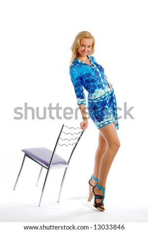 The beautiful blonde posing in photosession with a chair