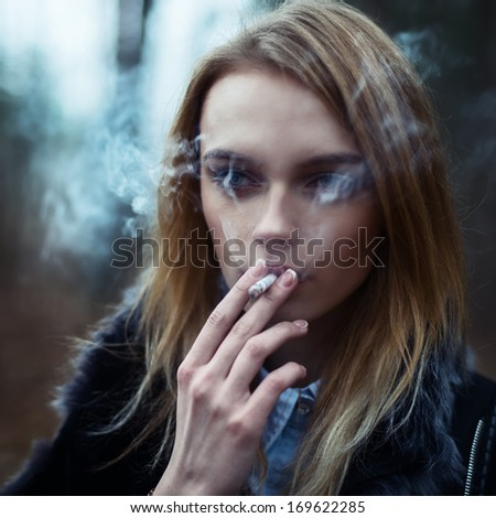 The beautiful blonde with a cigarette close-up smoking - stock photo