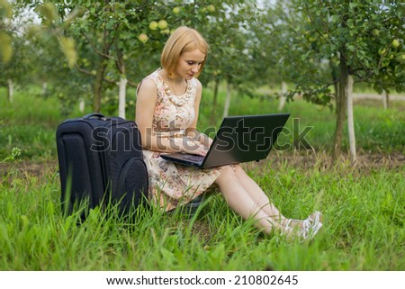 The beautiful blonde with a laptop on the nature